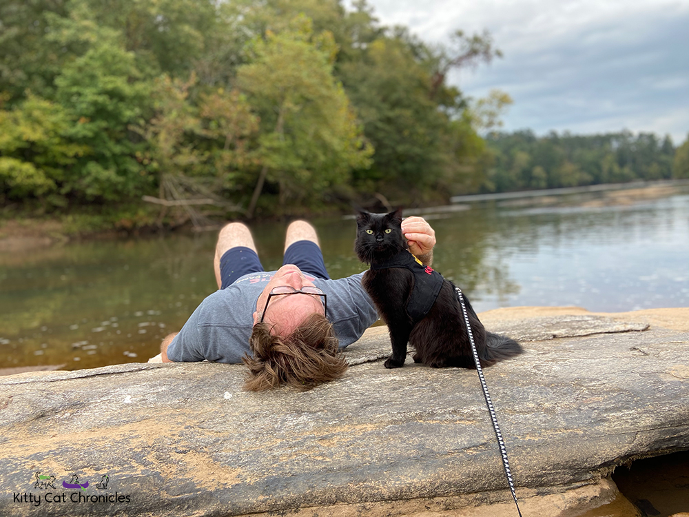 man and black cat beside the Ocmulgee River